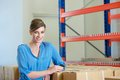 Female warehouse worker smiling smiling with boxes and packages indoors close up portrait of a Royalty Free Stock Images