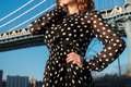Female wearing black and white polka dots dress posing outdoors in the city.