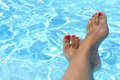 Female wet feet in the clear water of the pool Stock Photography