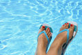 Female wet feet with flip flops by the pool Stock Photos