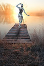 Female woman android robot sunrise sunset a cyborg machine is on a pier by the water looking at a or abstract technology idea Royalty Free Stock Image