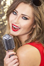 Female woman singing with vintage microphone beautiful singer into a microphoone on a night club Stock Image