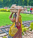 Female worker carries rock waste on her hat Royalty Free Stock Photo