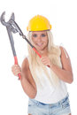 Female worker with pipe tongs sexy young blonde girl working as building labor a yellow helmet and gas pliers or Royalty Free Stock Image
