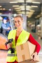 Female worker protective vest scanner holds package standing warehouse freight forwarding company smiling Stock Photo