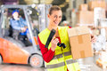 Female worker protective vest scanner holds package standing warehouse freight forwarding company smiling Stock Images