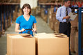 Female worker pulling pallet in warehouse looking to camera Stock Photo