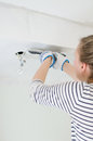 Female worker repairs gypsum plasterboard frame with spackling paste Stock Photos