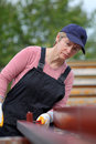 Female worker serious painting tube with paintroller real people selective focus and no retouching Royalty Free Stock Images