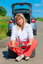 Female years sitting on a spare wheel near the car road Royalty Free Stock Photos