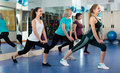 Females having group aerobic train positive smiling gymnastic class in fitness club selective focus Royalty Free Stock Images