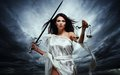 Femida goddess of justice with scales and sword against dramatic stormy sky Stock Photography