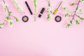 Feminine desk with cosmetic: lipstick, shadows, mascara and white spring flowers on pink background. Flat lay, top view. Beauty co Royalty Free Stock Photo