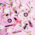 Feminine desk with woman cosmetics and white flowers on pink background. Flat lay, top view. Beauty concept for blog Royalty Free Stock Photo