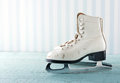 Feminine winter sports concept pair of white women s ice skates on blue vintage wooden background Royalty Free Stock Image