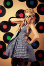 Femininity charming pin up woman with retro hairstyle and make up posing with vinyl record Royalty Free Stock Image