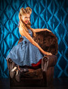 Femininity charming pin up woman with retro hairstyle and make up sitting in the armchair over vintage background Royalty Free Stock Photo
