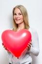 Femme blond retenant un ballon de coeur Photographie stock