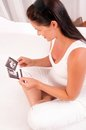 Femme de Ppregnant avec des photos de chéri sur le sofa à la maison Photos libres de droits