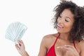 Femme de sourire de brune dirigeant une fan des notes du dollar Photographie stock libre de droits