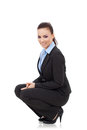 Femme souriant en position accroupie Photo stock