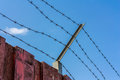 Fence with barbed wire and the blue sky Royalty Free Stock Photography