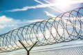 Fence with barbed wire in front of great blue sky concept for freedom liberty or prison Royalty Free Stock Photography