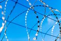 Fence with barbed wire in front of great blue sky concept for freedom liberty or prison Royalty Free Stock Photos