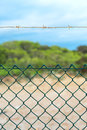 Fence with barbed wire under blue sky Stock Photography