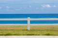 The fence on grassland and ocean view blue sky Royalty Free Stock Photo