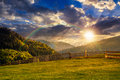 Fence through the grassy meadow in mountains at sunset with rain Royalty Free Stock Photo