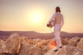 Fencer man standing on top of the rock holding fencing mask and a sword on sunset background back view Stock Photo