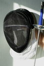 Fencing helmet and fencing sword on the light Stock Photos