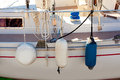 Fender buoys on sailboat side with ropes Stock Image