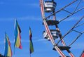Fereis wheel and flags ferris ride beside with blue sky Royalty Free Stock Photos