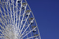 Ferris wheel blue and white against brilliant blue sky Royalty Free Stock Images