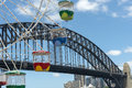 Ferris wheel at luna park with blue sky clouds and harbour bridge in the background sydney australia Royalty Free Stock Photography