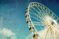Ferris wheel retro style image of a against blue sky cross processed grunge effect Royalty Free Stock Image