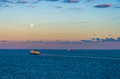 Ferry and large vessels at sea under a full moon Royalty Free Stock Photo