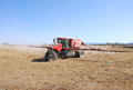 Fert spread fertilizer spreader with extended booms working an field in klamath falls basin area Royalty Free Stock Photography