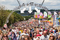 Festival crowds at glastonbury uk june large crowd of goers walking along a busy thoroughfare on a sunny day Stock Image