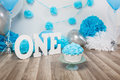 Festive background decoration for birthday celebration with gourmet cake, letters saying one and blue balloons in studio Royalty Free Stock Photo