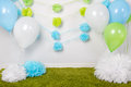Festive background decoration for first birthday celebration or easter holiday with blue, green and white paper flowers, balloons Royalty Free Stock Photo