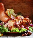 Festive baked chicken with autumn berries, fruits, nuts and vegetables in the rustic style of the old wooden