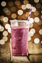 Festive blueberry smoothie blended with yogurt and ice cream for a refreshing summer drink against a bokeh of sparkling lights Stock Photography
