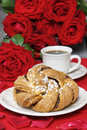 Festive braided bread on white plate rose petals around bouquet of roses in the background Royalty Free Stock Photo