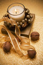 Festive candle surrounded by nuts and tape decorative candles on the table Royalty Free Stock Photos