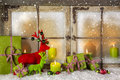 Festive christmas window decoration in green and red with presents and candles. Royalty Free Stock Photo