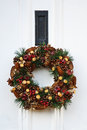 Festive christmas wreath on white door at xmas Stock Images