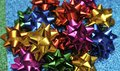 Festive colorful bows on sparkling glitter paper texture. Holiday background. Royalty Free Stock Photo